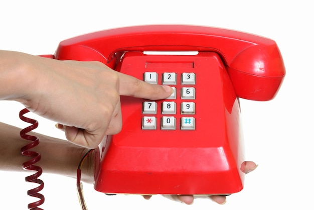Hand holding and dialing old telephone against white wall