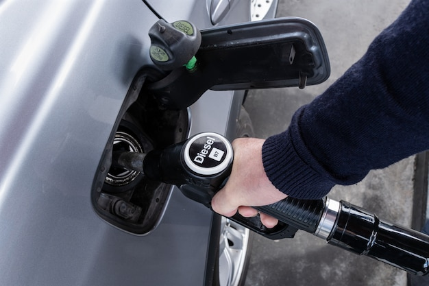 Hand holding diesel nozzle for car refueling at gas station