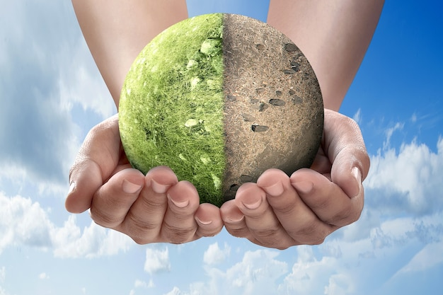Hand holding the difference between drought ground and fertile soil on the field on the earth. world environment day