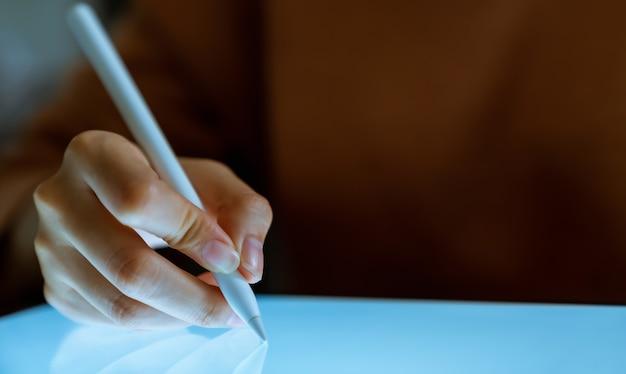 デジタルペンを持ってタブレットを使用し、空白の画面に触れる手。