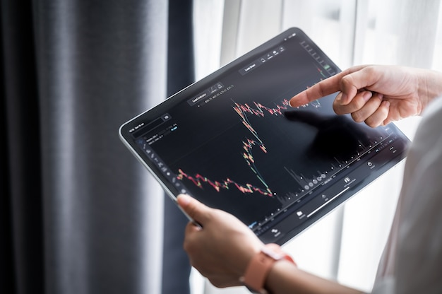 Hand holding digital tablet display stock market data with graph and chart for analyze and check before trading stocks online