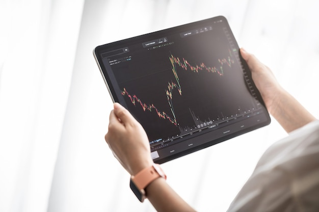 Hand holding digital tablet display stock market data with graph and chart for analyze
