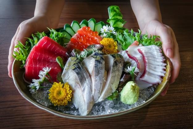 Hand holding  dish of japanese sashimi seafood set