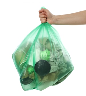 Hand holding disposable bag with different trash, isolated on white background