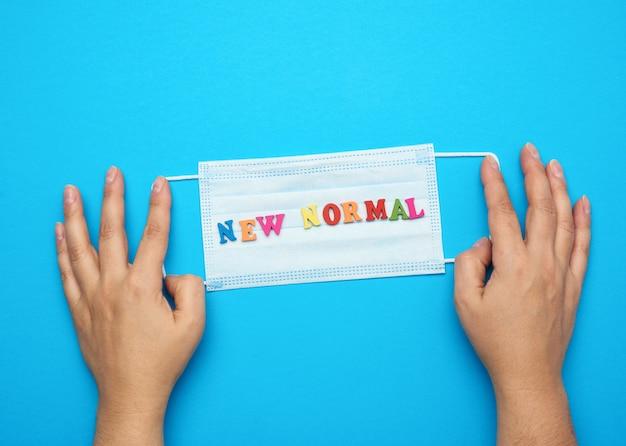 손을 잡고 일회용 의료 얼굴 마스크, 파란색에 새로운 정상 글자