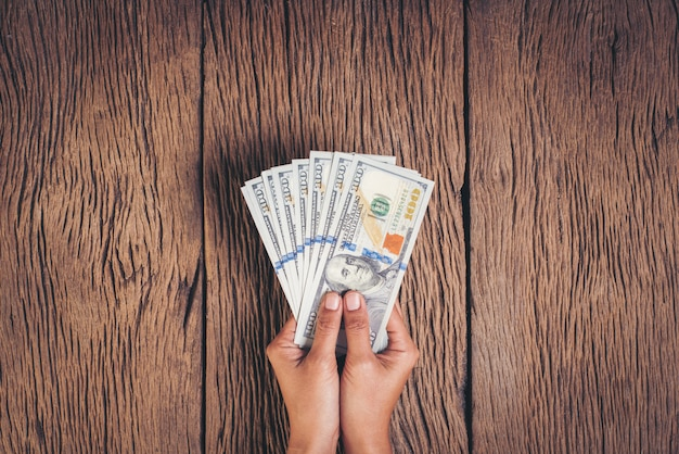 Hand holding dollar banknote money on wood background