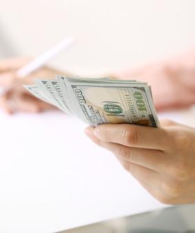 白い表面にドル紙幣を持っている手