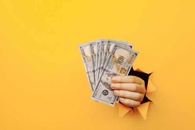 黄色い紙の穴からドル紙幣を持っている手