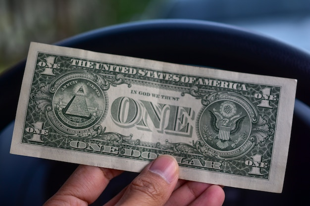 Hand holding dollar in car