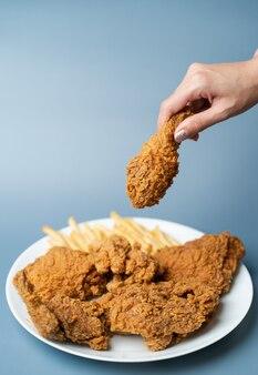 손을 잡고 나지만, 파란색 배경에 흰색 접시에 감자 튀김과 바삭한 프라이드 치킨.