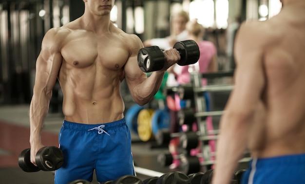 ダンベルを持っている手。クローズアップ。ジムで筋肉の腕。トレーニング、スポーツ、手、ダンベル、トレーニング。 -健康的なライフスタイルとフィットネスのコンセプト。フィットネスとスポーツに関する記事。