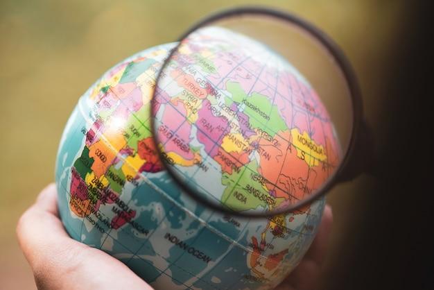 中東の上に地球の地球の球と拡大鏡を持っている手。
