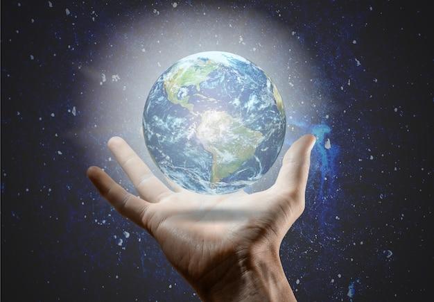 星と宇宙の背景に地球儀を持っている手