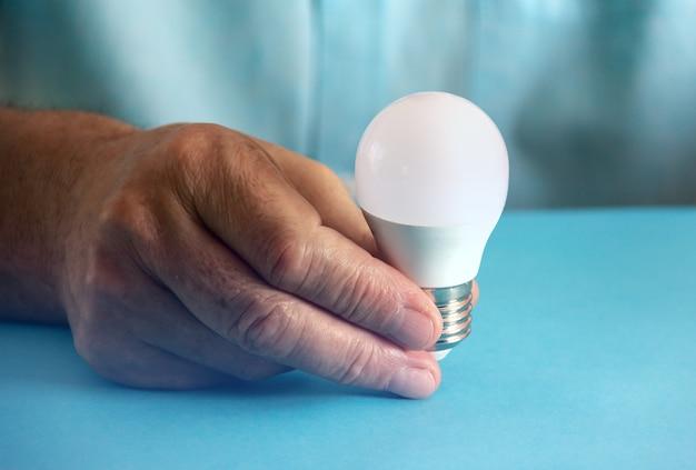 エコ電球を持っている手。電力消費量の節約。スペースをコピーします。セレクティブフォーカス。