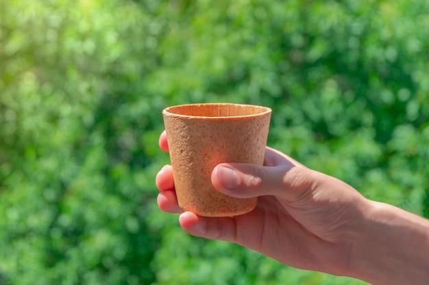 Рука, держащая съедобную вафельную кофейную чашку на зеленом фоне, концепция нулевых отходов