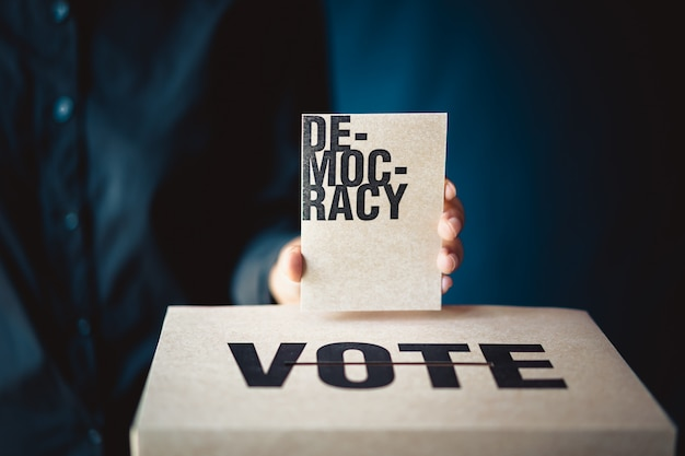 Вручите держать карточку выборов и ящик для голосования, концепцию демократии, ретро тон