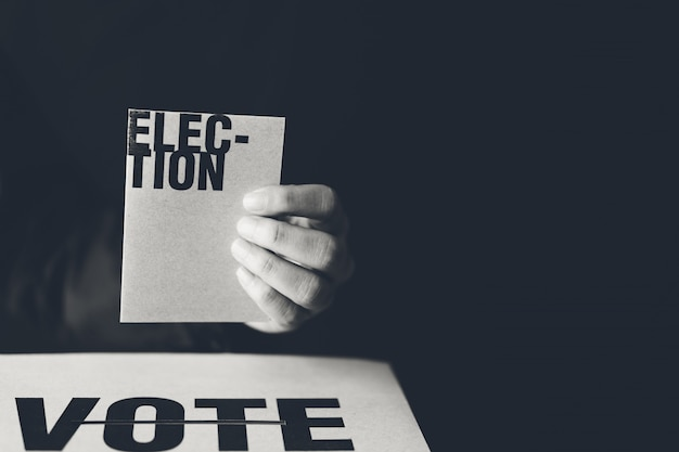 Hand holding election card and vote box, democracy concept, black and white tone