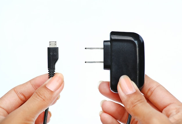 Hand holding electric plug and micro usb cable on white background