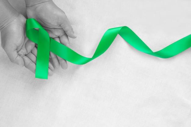 Рука, держащая изумрудно-зеленую или нефритовую зеленую ленту, скручивается на фоне белой ткани с копией пространства, символом осведомленности о раке печени, всемирным днем борьбы с раком. концепция здравоохранения или больницы и страхования.