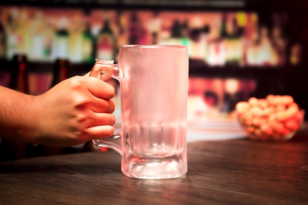 Hand holding empty beer glass