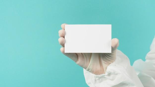 空の空白の白いカードを持っている手。ppeスーツ、緑またはティファニーブルーの背景にラテックス手袋をはめた手。テキスト用の空のスペース