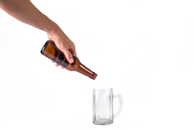 Hand holding an empty bottle of beer pouring on glass isolated a white background