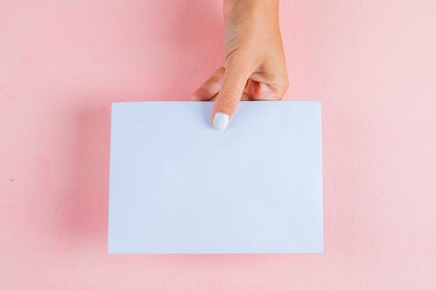 Рука держит пустую бумагу
