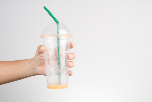 Hand holding empty plastic cup of thai milk ice tea with green straw