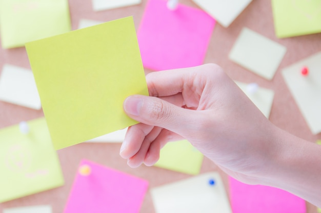 Hand holding empty post it paper or sticky note with blurred cork board background for insert your messages.