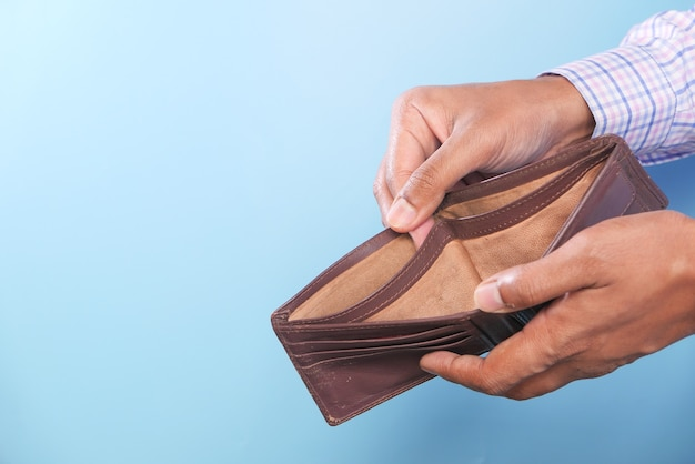 Hand holding empty wallet with copy space.