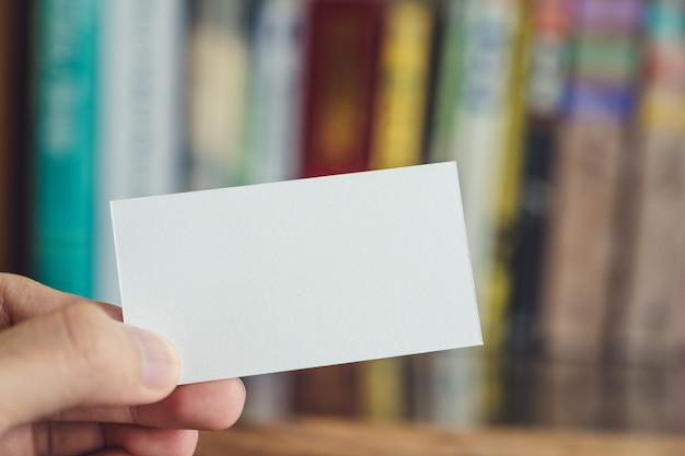 Hand holding empty white business card on wooden table and blur bookshelf in background