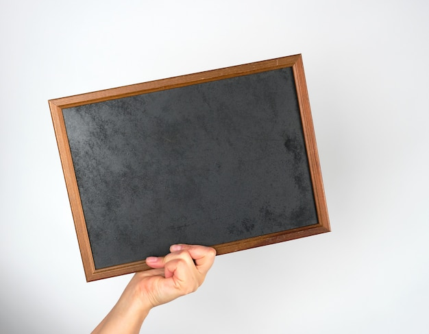 Hand holding an empty wooden chalk frame on gray