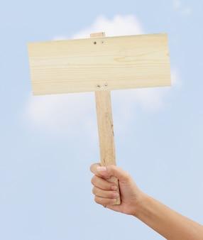 空の木製看板を持っている手