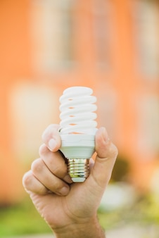 Hand holding energy saving compact fluorescent light bulb at outdoors