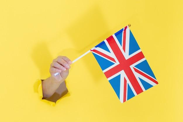 Рука, держащая английский флаг из желтой рваной бумаги. флаг соединенного королевства в руке.