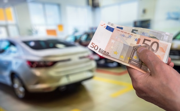 Hand holding euro banknotes in front of car