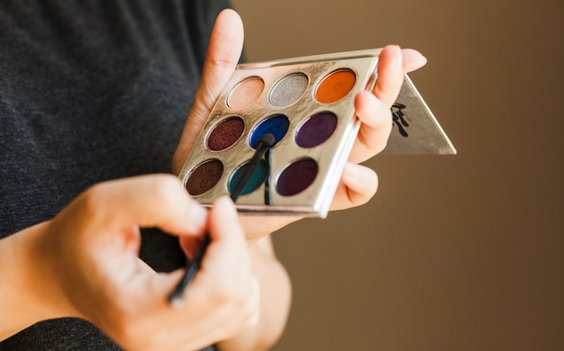 Hand holding eye shadow palette