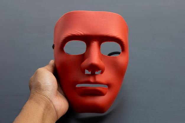 어두운 표면에 얼굴 마스크를 들고 손입니다.