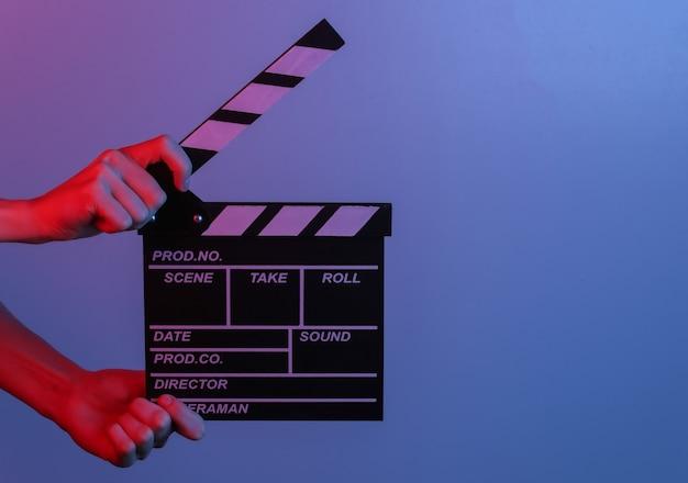 파란색 빨간색 네온 불빛에 손을 잡고 필름 클래퍼 보드. 영화 산업, 엔터테인먼트.
