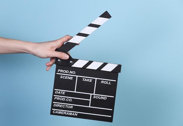 파란색 배경에 필름 클래퍼 보드를 들고 있는 손. 영화 산업, 엔터테인먼트.