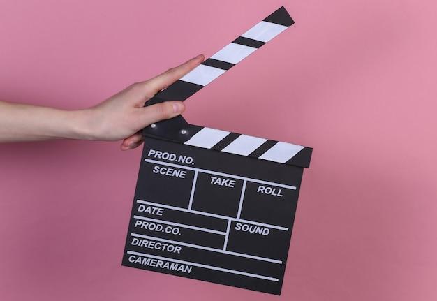 분홍색 배경에 필름 클래퍼 보드를 들고 있는 손. 영화 산업, 엔터테인먼트.