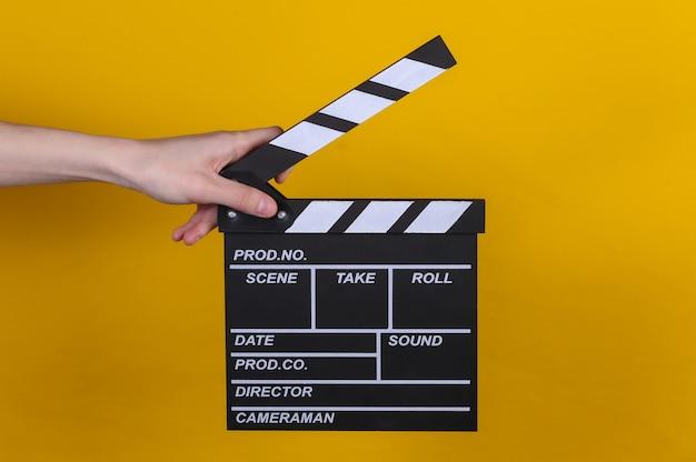 노란색 배경에 필름 클래퍼 보드를 들고 있는 손. 영화 산업, 엔터테인먼트.