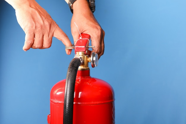 Hand holding fire extinguisher on blue background.