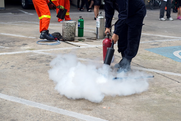 Hand holding fire extinguisher and spraying to the burning fire