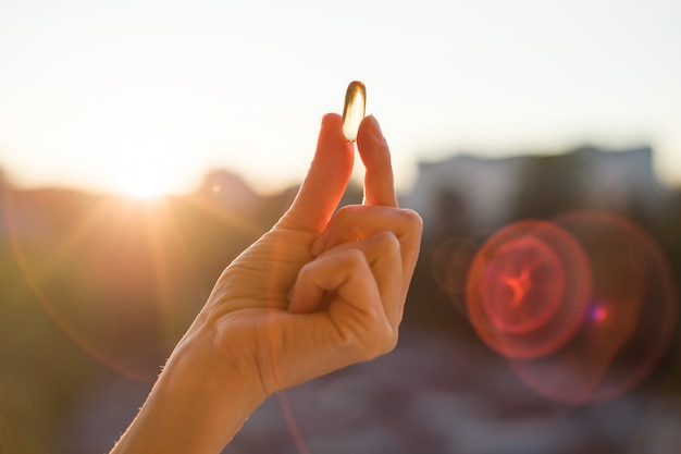 Hand holding fish oil omega-3 capsules, urban sunset background.