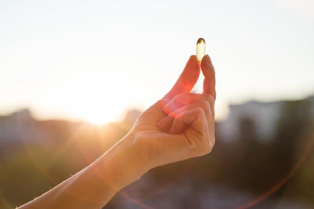 Hand holding fish oil omega-3 capsules