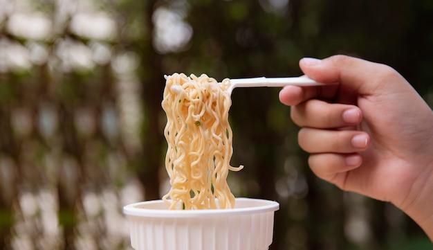 Hand holding fork take instant noodle