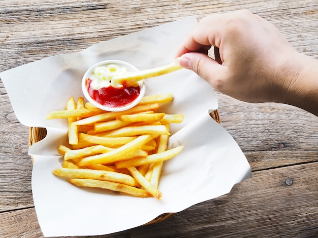 Hand holding french fries and dipping to ketchup