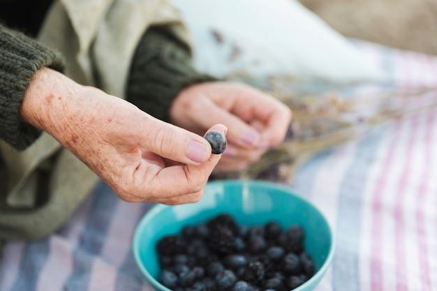 Hand holding fresh blueberry