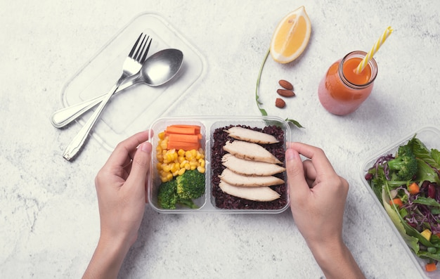 Hand holding fresh healthy diet lunch box with vegetable salad on table.